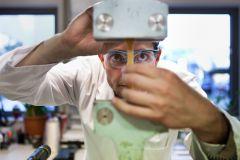 Jens Erdmann beim Einspannen eines Prüfstabes/Knochen in die Zugprüfmaschine. Nach dem Einspannen wird der Prüfkörper auseinander gezogen bis er bricht, wobei die maximale dafür aufgewendete Kraft gemessen wird (Zugversuch). Diese Kraft ist ein Maß für di